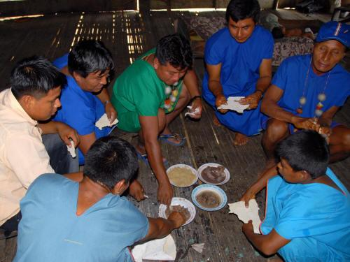 COFAN TRIBE HISTORY: Cofan men eating traditional food.