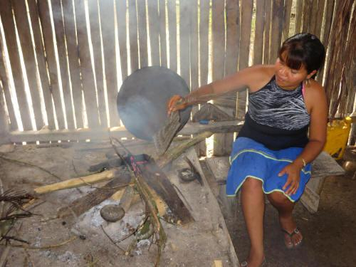 TURISMO ORIENTE DEL ECUADOR: Siona woman cooking on traditional fire box.